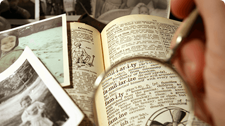 Old photos and a dictionary seen through a magnifying glass.
